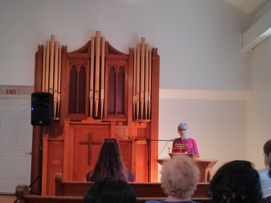Jane Munro reading in the church at Eden Mills. Also pictured: the backs of Liz Howard's & Kitty Lewis's heads.